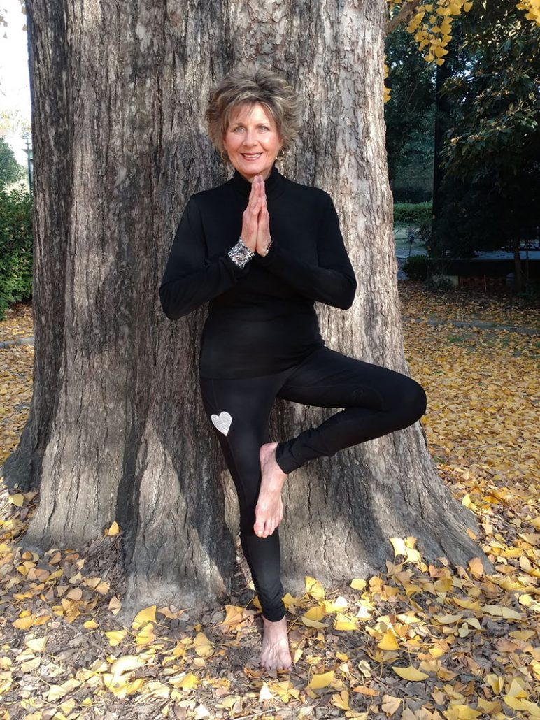 Photo of Mary Ellen Smith in yoga pose leaning against a tree